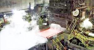千葉県の新日鉄住金君津製鉄所内の熱延工場でスラブがローラーを通過しながら水蒸気を発している。(新日鉄住金提供)