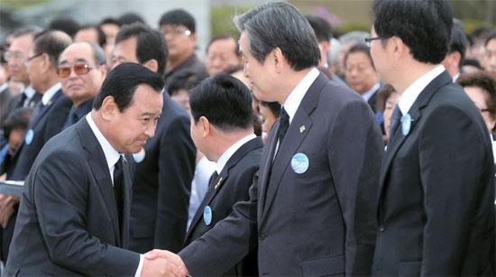 李完九首相(左)が19日、ソウル水踰洞(スユドン)の国立4・19民主墓地で開かれた4・19革命記念式開始前に金武星(キム・ムソン)セヌリ党代表と握手している。2人の間に会話はなかった。イ・ソクヒョン国会副議長(左から2人目)が「大統領に業務報告をするか」と尋ねると李首相は「秘書室長がしている」と答えた。