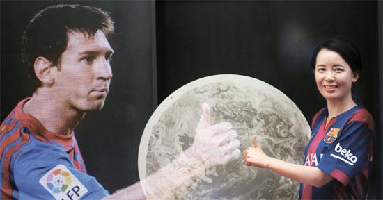 韓国人画家のキム・ヒョンソンさん(右)はサッカーで受けたインスピレーションを作品に表現する。彼女はリオネル・メッシを見るたびに強さと柔らかさ、鋭さなどさまざまな感じを受けるという。メッシに誕生日プレゼントとして贈る作品「沈墨」を持つキムさんとメッシの映像を多重撮影した写真。