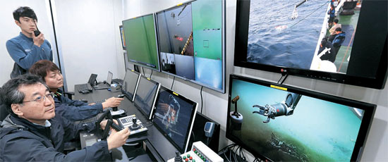 韓国海洋科学技術院の研究員、ペク・セフンさん、キム・バンヒョンさん、キム・ウンソさん(後方から)が18日、巨済島の南海研究所で深海用の遠隔無人操縦潜水艇(ROV)「ヘミレ」を操縦し、性能テストをしている。