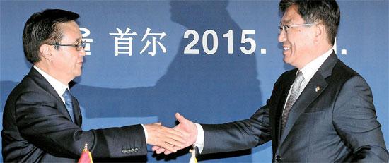 尹相直(ユン・サンジク)産業通商資源部長官(右)と高虎城中国商務相が1日、ソウルグランドハイアットホテルで韓中自由貿易協定書に署名した後、握手している。