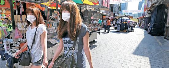 7日、ショッピング客2人が人が少ないなソウル南大門市場を歩いている。日曜日午後は混雑する時間だが、MERSの拡散以降、客は半分以上減っている。