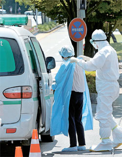 10日午後、救急車でサムスンソウル病院に到着した患者が医療スタッフの助けを受けて防護服を着ている。この日午前現在の中東呼吸器症候群(MERS)確診患者は13人増えて計108人になった。