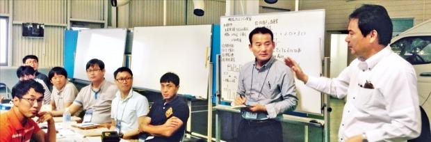 韓国中小企業の関係者が、トヨタ自動車系列会社の岐阜車体工業訓練センターで、山下広也取締役(右)から浪費を減らす要因に関する説明を聞いている。