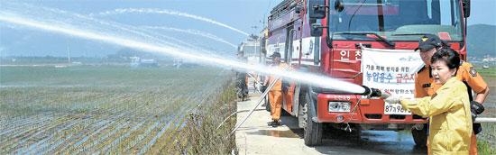 21日午前、仁川市江華郡華道面興旺里を訪問して消防隊員と共に乾いた畑に水をかけている朴槿恵大統領。(写真=江華/青瓦台写真記者団)