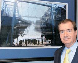 執務室の壁にかかった韓国哨戒艦「天安」の残骸写真の前に立つエド・ロイス米下院外交委員長。