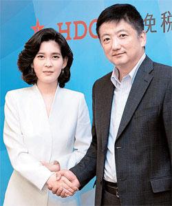 30日に中国最大の旅行会社の中国旅行総社北京本社を訪問したホテル新羅の李富真社長(左)が中国旅行総社の薛曉崗総裁と握手している。(写真=ホテル新羅)