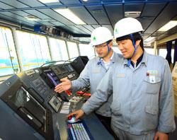 現代重工業の従業員がスマートシップシステムを装着した船舶の操舵室をチェックしている。(写真=現代重工業)