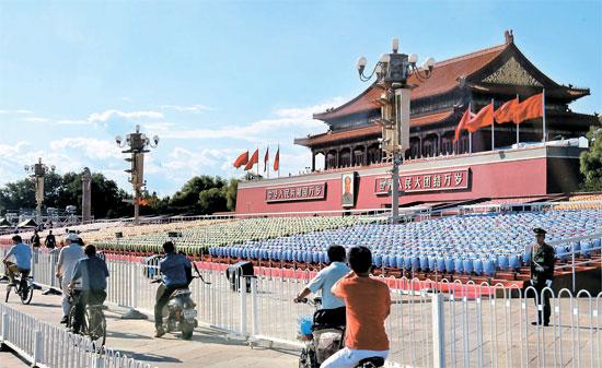 「抗日戦争・反ファシスト戦勝70周年」記念行事を翌日に控えた2日、中国北京天安門広場に設置されたバリケードの間を市民が通過している。中国政府はこの日から臨時公休日に指定した3日まで天安門広場と長安街一帯の建物の出入りを統制し、地下鉄駅など大衆施設の検問検索を強化した。
