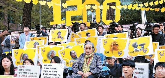 14日、ソウル中学洞の旧駐韓日本大使館前で開かれた旧日本軍「慰安婦問題解決のための第1200回水曜集会」で、金福童さんをはじめ、参加者がプラカードを持ってデモを行っている。