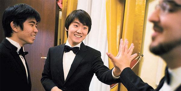 21日(現地時間)、ポーランドのワルシャワ・フィルハーモニーコンサートホールで開かれた「第17回ショパン国際ピアノコンクール」授賞式会場で優勝者チョ・ソンジン氏が2位となったカナダのシャルル・リシャール=アムラン氏と手をあわせている。(写真=ショパン国際コンクール2015)