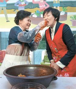 日本の安倍晋首相の夫人・昭恵氏が5日、東京の韓国大使館で柳興洙(ユ・フンス)駐日韓国大使夫人のパク・ヘジャ氏が口に入れてくれたキムチを味わっている。(写真=在日韓国大使館)