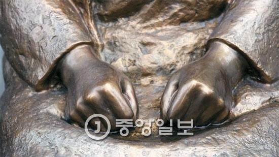 在韓日本大使館の前にある慰安婦平和碑(少女像)の手。両手を固く握っている。