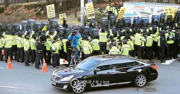日本軍の慰安婦問題解決のための韓日外相会談が開かれた28日午後、ソウル都染洞(ドリョムドン)の外交部庁舎前で「平和と統一を開く人々」をはじめとする市民団体の会員らが日本糾弾デモを行った。会談を終えた日本の岸田文雄外相が乗った車両が警察に囲まれたデモ隊の前を通り過ぎていった。