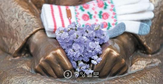 3日、ソウルの在韓日本大使館の前にある「平和の少女像」の握られた手の上に花と手袋が置かれている。