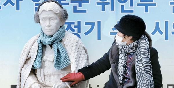 6日、ソウル中学洞(チュンハクトン)駐韓日本大使館の前で開かれた第1212回目の集会で李容洙(イ・ヨンス)さんが故金学順(キム・ハクスン)さんの石膏像に触れている。