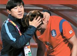 日本戦で逆転負けを喫した後、MFパク・ヨンウを慰める申台龍監督(左)。(写真=大韓サッカー協会)