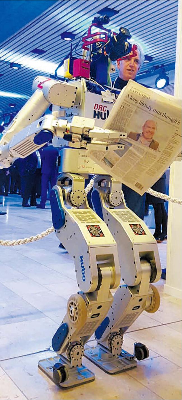 ダボスフォーラムに招待されたKAIST(韓国科学技術院)のヒューマノイドロボットHUBOが先月21日(現地時間)、自分の記事が掲載された英フィナンシャルタイムズ新聞を読んでいる。(写真=呉俊鎬教授)