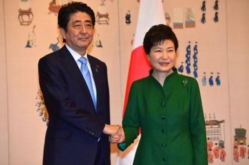 2015年11月に朴槿恵(パク・クネ)大統領と日本の安倍晋三首相が青瓦台(チョンワデ、大統領府)で記念撮影をしながら握手している。(写真=青瓦台写真記者団)