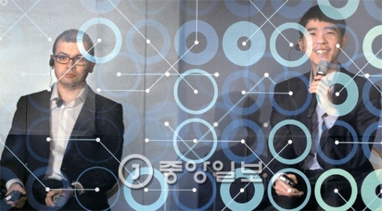 李世ドル九段(右)が8日に「アルファ碁」との対局を翌日に控え記者会見をしている(多重撮影)。左側はグーグルディープマインドのデミス・ハサビスCEO。