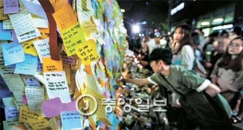 17日に江南(カンナム)駅近隣のビルの共用トイレで殺害された20代女性の追悼に訪れる人々が19日の夜遅くまで続いている。