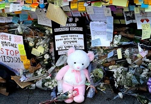 ソウル地下鉄の江南(カンナム)駅10番出口のガラスの壁の前に19日、市民が持ってきて置いたクマのぬいぐるみと花が置かれている。
