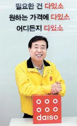 朴正夫会長が本社地下のダイソー道谷(トゴク)店のレジの前に立っている。背後には新しいスローガンが見える。