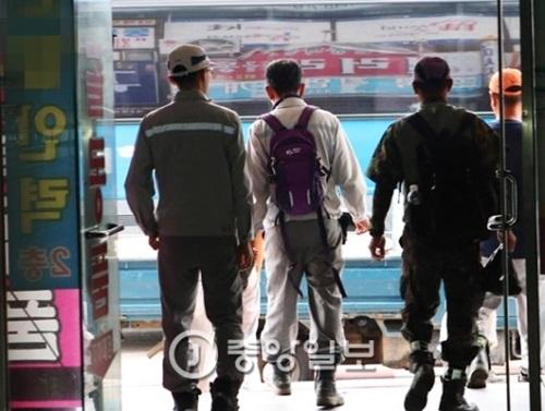 7日午前、慶尚南道巨済市のある人材派遣業者から造船所の作業服を着た人たちがマンション工事現場に移動するため建物を出ている。50カ所ほどある人材派遣業者の求職者のうち10~20%が造船所の労働者出身だ。造船所の構造調整の余波で彼らはマンションなどの建設現場で日当を受け取って働く。