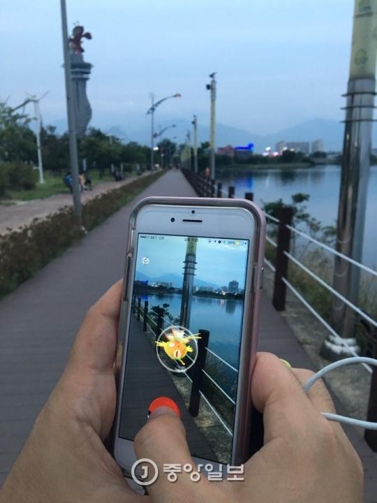 13日、江原道束草市のエキスポ公園であるゲーマーがスマートフォンに現れた「ポケモン」を捕まえている。