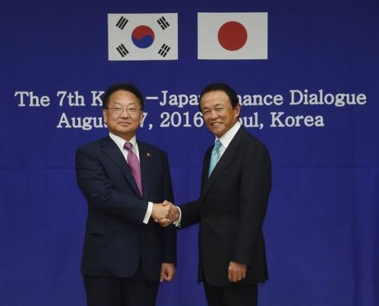 27日に政府ソウル庁舎で開かれる韓日財務相対話に先立ち柳一鎬副首相兼企画財政部長官と麻生太郎財務相が握手している。この日韓日政府は通貨スワップ協定を再開することで合意した。(写真=企画財政部)