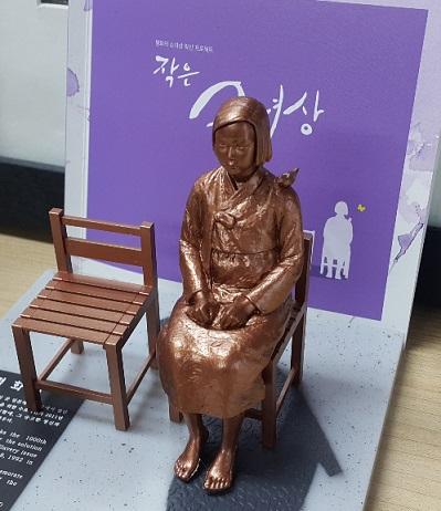 慰安婦少女像を製作した彫刻家のキム・ウンソン、キム・ソギョン夫妻がソウル中学洞(チュンハクトン)の日本大使館前の少女像に市民が着せた服と耳あてを直している。(写真=中央フォト)