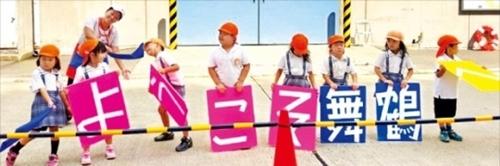 京都市から北に90キロ離れた舞鶴港。埠頭で幼稚園児がクルーズ船観光客を迎えている。