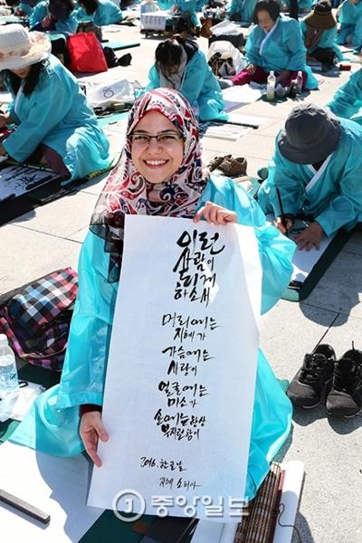 エジプトから来たソフィアさん(30)が、自身が書いた筆文字を上げて見せている。