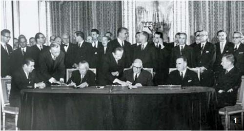 1963年1月22日、仏エリゼ宮でアデナウアー西ドイツ首相(正面を向いて座っている人のうち左側)とドゴール仏大統領(真ん中)が両国の友好条約に署名している姿を、ポンピドゥー仏首相(右)が眺めている。