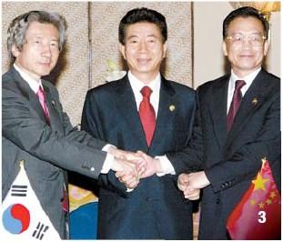 2003年10月7日、盧武鉉(ノ・ムヒョン)大統領(真ん中)と温家宝中国首相(右)、小泉純一郎首相がインドネシア・バリで開催された韓日中首脳会談を終えた後、条約に署名して握手している