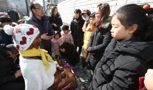 ことし1月、家族単位の市民が釜山東区庁の日本領事館前に建設された少女像を訪れて記念撮影をしている。