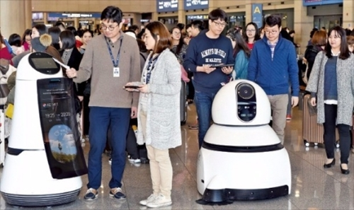 LGエレクトロニクスの研究員が仁川国際空港入国フロアで案内ロボット(左)と清掃ロボットをテストしている。