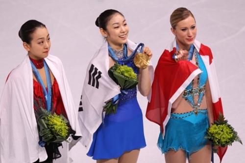 2010年2月25日(韓国時間)、バンクーバーのパシフィック・コロシアムで開かれた冬季オリンピックのフィギュアスケート授賞式でキム・ヨナが金メダルを首にかけ、浅田真央(左)、ジョアニー・ロシェットとファンたちに挨拶している。