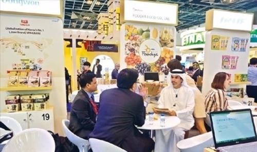 韓国食品企業の職員が2月26日、アラブ首長国連邦(UAE)ドバイで開催された「2017ドバイ食品博覧会」で現地バイヤーに製品を説明している。(写真=aT提供)