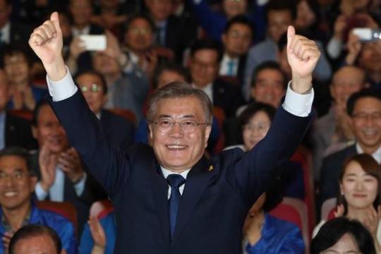 写真=文在寅候補が9日午後、ソウル汝矣島(ヨイド)国会議員会館に設置された共に民主党の開票状況室で、党関係者の歓呼に両手をあげて応えている。