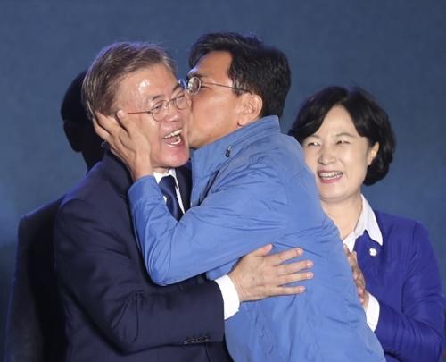 9日、ソウル光化門広場で開かれた文在寅大統領当選記念行事で安熙正忠南知事(右)が文大統領にキスをしている。(写真=中央フォト)