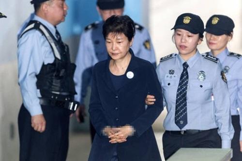 朴槿恵前大統領が23日、ソウル中央地裁で開かれた初公判に出席するために護送車から降りて移動している。