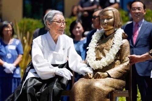2013年7月30日に米カリフォルニア州グレンデール市に設置された慰安婦平和の少女像の手を、慰安婦被害者の金福童(キム・ボクドン)さんが握っている。(写真=中央フォト)