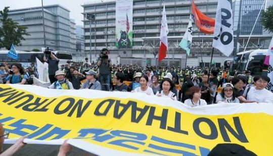 24日午後にソウル広場で開かれた「THAAD撤回平和行動集会」の参加者が駐韓米国大使館前で「THAAD強要米国糾弾、NO THAAD NO TRUMP」と書いた垂れ幕を持ってスローガンを叫んでいる。2000人余りの参加者は19分間にわたり大使館を囲みデモを行った。