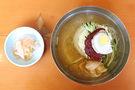 ミルミョンは、小麦粉で作ったもっちりとした麺を、肉でダシをとったスープで食べる一品。麺の上にトッピングされたニンニクや唐辛子ベースの薬味をスープとよく混ぜ合わせると、さっぱりピリ辛スープに仕上がります。