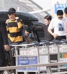 28日、仁川国際空港に到着したボーイズグループ防弾少年団。黄と黒の縞模様のシャツを来たメンバーのジンが遠くを見つめている。