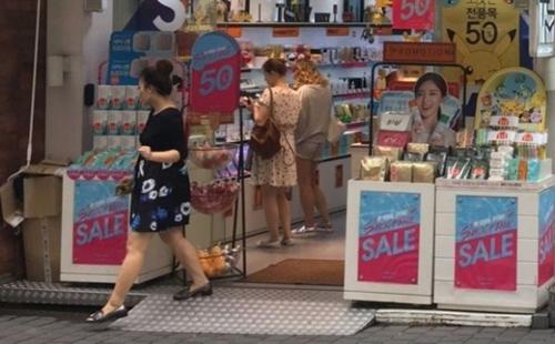ソウル・明洞のある化粧品ショップが冷房をつけた状態で営業している。ワゴンがドアの敷居にまたがっておりドアを開け閉めすることはできない状態だ。
