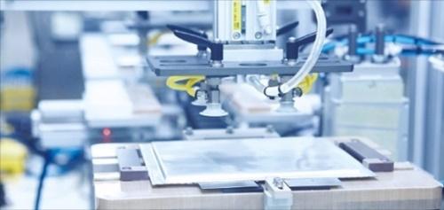忠南瑞山市SKイノベーション電気車バッテリー工場でロボットが銀色のパウチで包装されたバッテリーセルをパック工程に移送するために準備中だ。(写真=SKイノベーション)