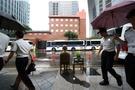 1000回目の水曜集会を記念するために建てられた少女像が語ることなく凝視する中で2012年8月に旧日本大使館周辺を警察がパトロールしている。