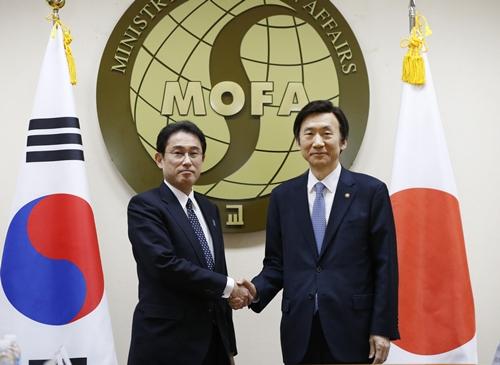 2015年12月28日、ソウル外交部庁舎で韓国の尹炳世(ユン・ビョンセ)外交部長官(右)と日本の岸田文雄外相が慰安婦問題の解決策をさぐる会談に先立ち、握手をしている。